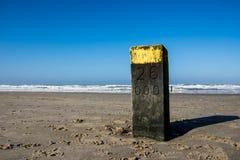 Poteau en bois sur la plage néerlandaise images stock