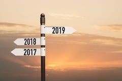poteau indicateur de la nouvelle année 2019 heureuse, ciel de coucher du soleil d'ouverture de session de route et nuages photos stock