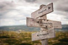 Poteau indicateur en bois de l'anglais, espagnol et français dehors photographie stock libre de droits