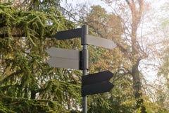 Poteau indicateur foncé vide en métal en parc naturel photos stock