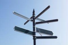 Poteau indicateur se dirigeant dans beaucoup de directions contre le ciel bleu photo libre de droits