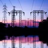 Poteau électrique, courrier à haute tension et ciel dans le temps crépusculaire Photographie stock