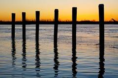 Poteaux de fleuve au coucher du soleil images stock
