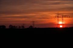 Poteaux de puissance dans le coucher du soleil Photographie stock