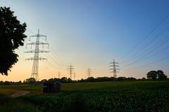 Poteaux de puissance dans un coucher du soleil images libres de droits