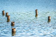 Poteaux en métal dans l'eau Photos libres de droits