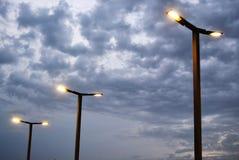Poteaux légers contre un ciel nuageux images stock