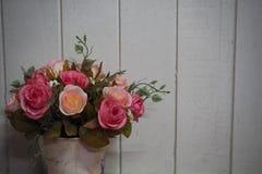Potenciômetro com fundo de madeira branco da prancha das rosas fotografia de stock