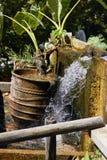 Potenciômetro de argila velho com planta verde e a fonte pequena decorativa da cachoeira foto de stock