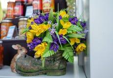 Potenciômetro de flor cerâmico com flores sob a forma de uma bota velha fotografia de stock royalty free