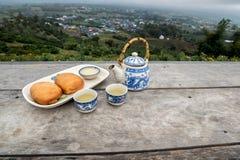 Potenciômetro do chá com o copo ajustado e o Fried Steamed Bun na tabela de madeira na frente do Mountain View imagens de stock