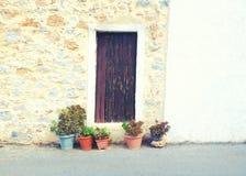 potenciômetros de flor e porta de madeira velha na rua acolhedor pequena Foto de Stock