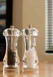 Potenciômetros de sal e de pimenta na tabela de cozinha Fotografia de Stock Royalty Free