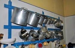 Potenciômetros e bandejas que penduram na parede em uma cozinha velha imagens de stock