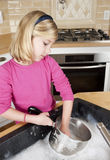 Potenciômetros e pratos da limpeza da menina imagem de stock