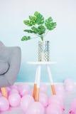 Potenciômetro com uma flor Monstera na mesa de centro branca Balões cor-de-rosa no assoalho foto de stock