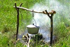 Potenciômetro com uma tampa no fogo Foto de Stock Royalty Free