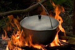 Potenciômetro com uma tampa no fogo Fotografia de Stock