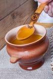 Potenciômetro de argila com ghee e colher no guardanapo de linho Ainda vida rústica Foto de Stock Royalty Free