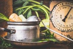 Potenciômetro de cozimento velho com vegetais crus e concha na mesa de cozinha rústica Imagem de Stock