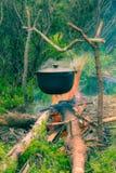 Potenciômetro de ebulição na fogueira no piquenique Imagem de Stock