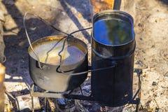 Potenciômetro do fundo dois com água caloroso no fogo durante uma viagem de acampamento fotografia de stock royalty free