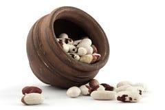 Potenciômetro do produto de cerâmica com os feijões no fundo branco Imagem de Stock
