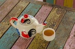 Potenciômetro e copo do chá na tabela de madeira Fotografia de Stock