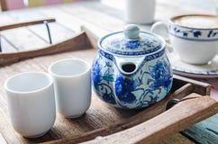 Potenciômetro e copos do chá na bandeja de madeira Foto de Stock