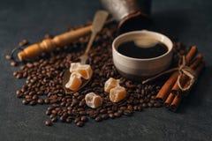 Potenciômetro fresco do café com açúcar de bastão e grões roasted Em um preto Imagem de Stock