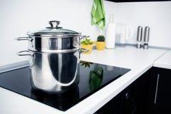 Potenciômetro na cozinha moderna com fogão da indução imagem de stock