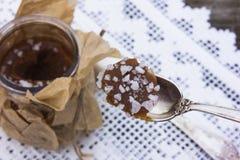 Potenciômetro salgado do caramelo com uma colher de prata Imagens de Stock Royalty Free