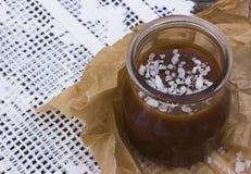 Potenciômetro salgado do caramelo com uma colher de prata vintage Imagens de Stock
