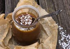 Potenciômetro salgado do caramelo com uma colher de prata vintage Fotografia de Stock