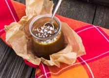 Potenciômetro salgado do caramelo com uma colher de prata vintage Fundo de madeira Vista de acima Fotos de Stock