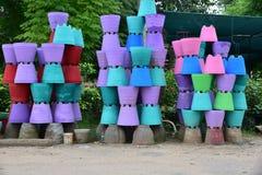 Potenciômetros de flor coloridos do cimento empilhados acima no lado da estrada Foto de Stock