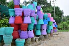 Potenciômetros de flor coloridos do cimento empilhados acima no lado da estrada Fotos de Stock Royalty Free