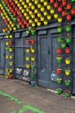 Potenciômetros de flor coloridos na parede da construção Fotos de Stock