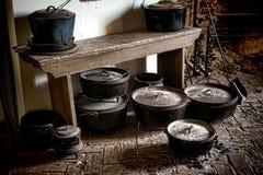 Potenciômetros e bandejas do ferro fundido do vintage na cozinha antiga Fotos de Stock Royalty Free