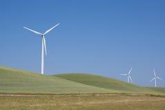 Potencia múltiple que genera los molinoes de viento detrás de las colinas Fotografía de archivo libre de regalías