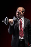 Potency. A serious businessman wearing a suit and lifting two heavy weight Royalty Free Stock Photo