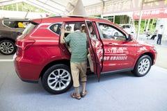 Potentiële koper die een Haval-merk Chinees automobiel SUV op vertoning inspecteren bij Dongguan-autotentoonstelling Stock Afbeelding