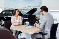 Potentiële vrouwelijke voertuigkoper die zorgvuldig aan autohandelaar luisteren stock afbeeldingen