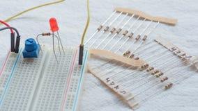 Potentiometer, weerstanden en rode LEIDENE opstelling op een broodplank stock foto