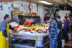 Potentional buyer looking at fish in small shop with sea products in Chinatown in Manhattan stock images