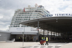 Poter with trolley and cruise ship Stock Photos