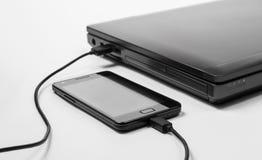 Potere di carico di Smartphone da un computer portatile immagini stock