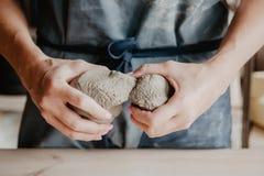 Poterie, argile, concept d'art de céramique - plan rapproché sur des mains de jeune maître avec les grands morceaux d'argile réfr photographie stock libre de droits