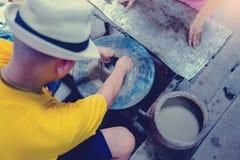 Poterie, atelier, concept d'art de céramique - le plan rapproché sur les mains masculines sculptent le nouvel ustensile avec les  photographie stock