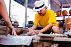 Poterie, atelier, concept d'art de céramique - le plan rapproché sur les mains masculines sculptent le nouvel ustensile avec les  image stock